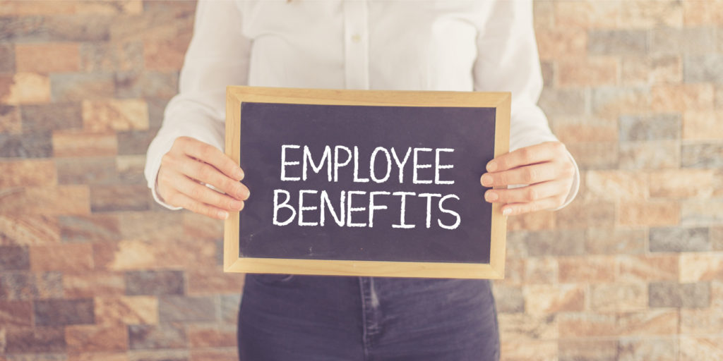 an employee of a company that has self-funded insurance holds a board with the text employee benefits