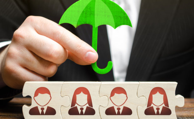 insurance broker explains self-funded insurance to employer by holding miniature umbrella over the blocks