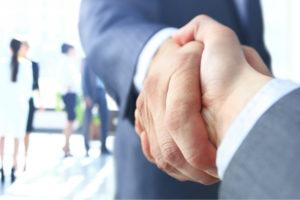prospective employee shake hands with company employee before they negotiate employee benefits