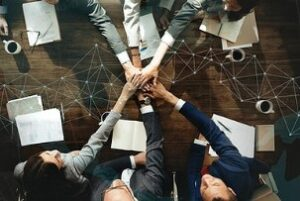 Business People Stacking Hands Together after knowing how to enhance company benefits