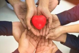 Group of Hands Holding Red Heart after knowing how does group health insurance work