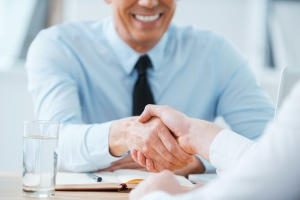 shaking hands with a benefits broker for new business