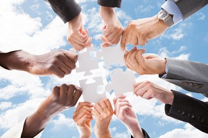 business people assembling jigsaw puzzle about Group Health Insurance