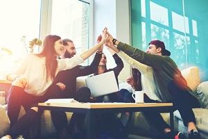 female and male elassmates celebrating office project success