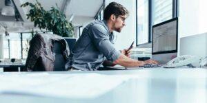 man at computer looking up benchmarking analysis