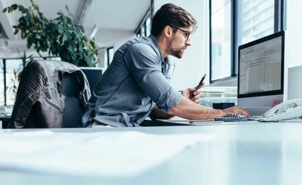 man at computer looking up benefits benchmarking