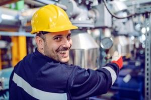 hardworking energy plant worker in working suit screwing valve