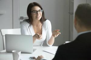 women talking through a HRIS System to employer