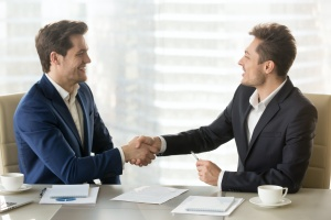 businessman hand shaking after learning about Level Funding