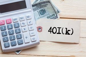 401k written on note with calculator and dollars