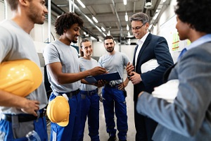 engineer and factory workers going through production reports about benefits plan
