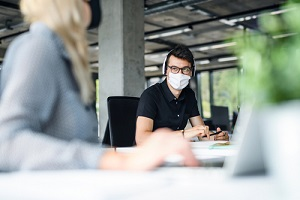 young people who are retain employees with face masks back at work in office after lockdown